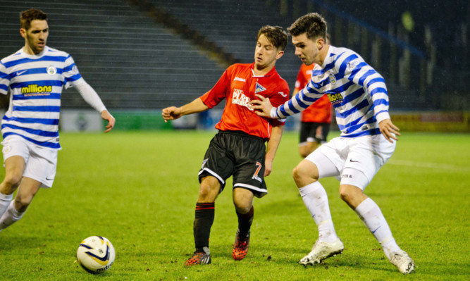 Dunfermline captain Josh Falkingham is shoved off the ball as the Pars try to find a way past the Morton defence.