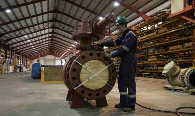 A Scores employee inspecting a valve