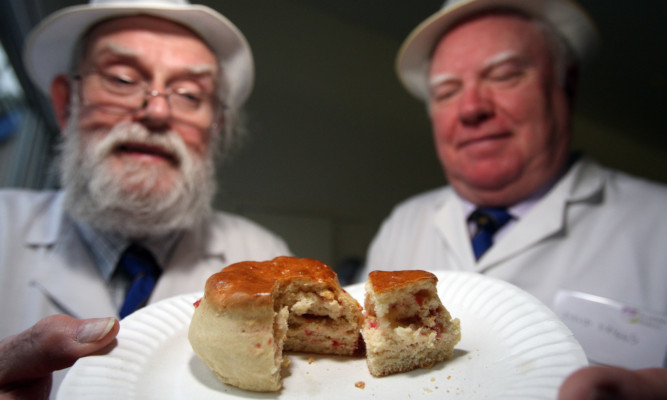 John Young and David Briggs check out the competition at the Scottish Baker of the Year 2013 competition .