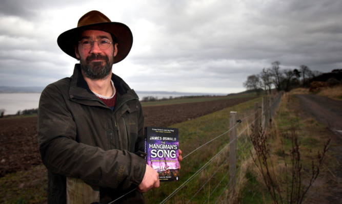 James Oswald on his farm with one of his popular Detective McLean novels.