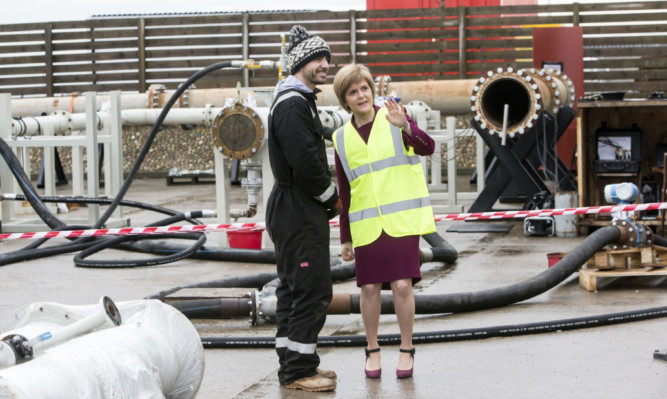 First Minister Nicola Sturgeon talks to technical specialist Euan Gibbons during a visit to pipeline support service provider Pipelines 2 Data in Aberdeen.