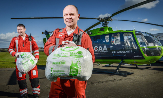 SCAA paramedics Craig McDonald, left, and John Salmond with a couple of Clothes Aid bags of unwanted garments.