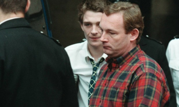 Andrew Drummond (in red shirt) is led away to serve his seven-year jail sentence for theft in 2002.