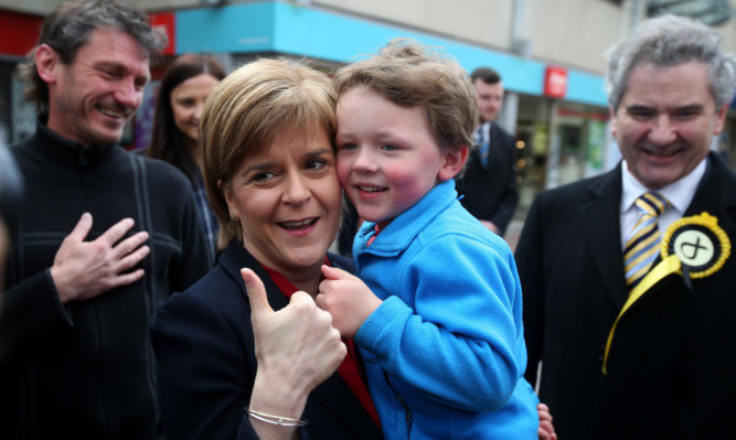 Scotland's First Minister and SNP leader Nicola Sturgeon with a young supporter on the General Election campaign trail in Kirkcaldy.