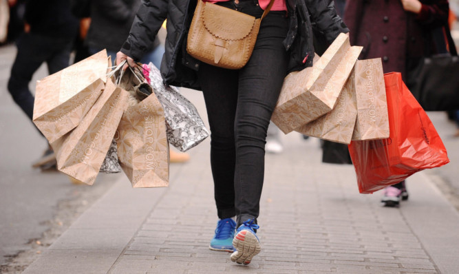"File photo dated 6/12/11 of a shopper carrying shopping bags. High street sales dropped by 2.2% last month in an ""underwhelming"" Christmas for many retailers, according to a report. ... High street sales ... 06-01-2014 ... London ... UK ... Photo credit should read: Dominic Lipinski/PA Wire. Unique Reference No. 18604411 ... Issue date: Monday January 6, 2014. Figures from accountancy firm BDO showed the sales surge hoped for by many shops failed to materialise in the crucial trading period, with like-for-like sales - excluding online trade - dropping by as much as 6.7% in the week to December 22. See PA story ECONOMY Retail. Photo credit should read: Dominic Lipinski/PA Wire"