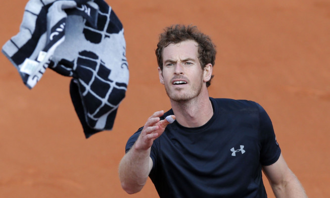 Andy Murray throws his towel to spectators after beating Argentina's Facundo Arguello in three sets.