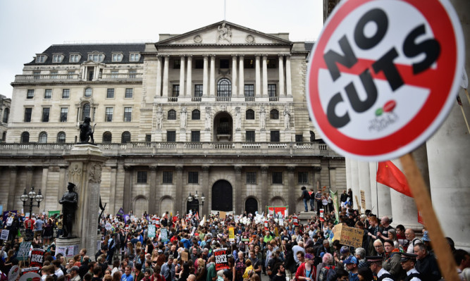Protestors march through central London during a demonstration against austerity and spending cuts.