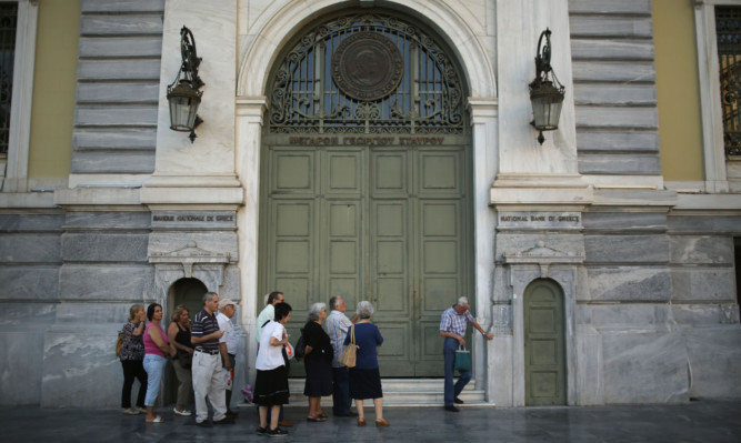 Senior citizens queue up to collect their pensions outside a National Bank of Greece branch in Kotzia Square in Athens.