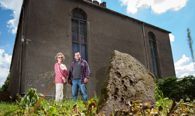 Crieff community councillor Craig Finlay with Jess Smith beside one of the stump stones at St Michaels Church graveyard.