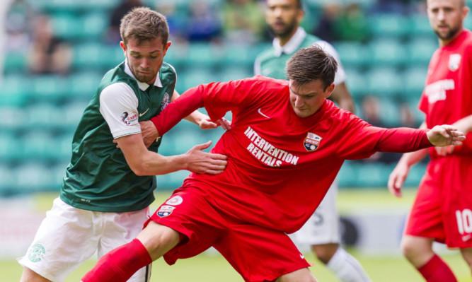 Montroses Scott Johnston battles for possession with Sam Stanton of Hibs.
