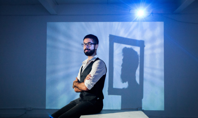 Artist Khaled Bahrami sits in his exhibition, called Altered Consciousness.