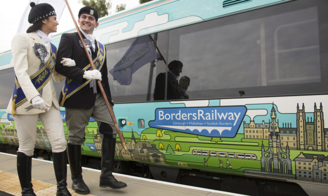 Braw Lad Cameron Pate and Braw Lass Abbie Franklin at the Tweedbank railway station to welcome a Borders Railway carriage