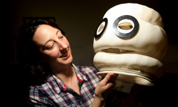 conservator Rebecca Jackson-Hunt gets to grips with the head of a Michelin Man suit.