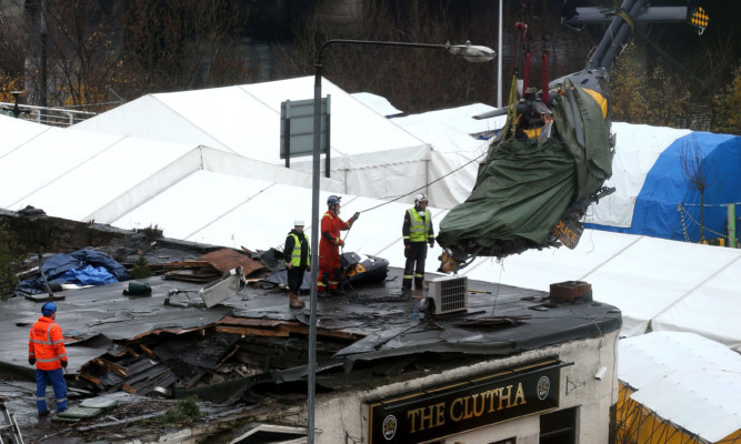 The helicopter wreckage being lifted out of the Clutha pub.