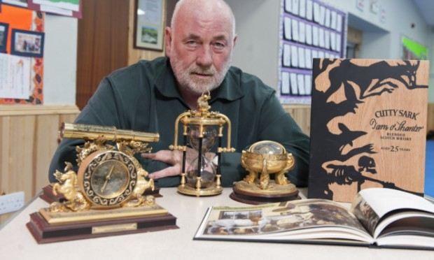 Dave Ramsay with some of the auction items for the memorial dinner later this month.