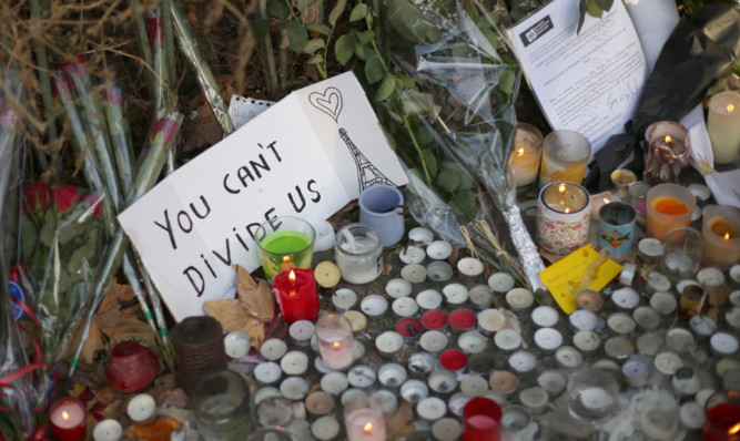 Flowers and tributes are left close to the Bataclan concert hall, Paris.