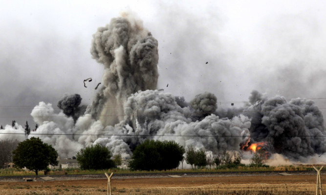 Smoke rises after an air strike on the Syrian town of Kobani late last year.