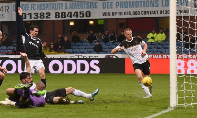Aberdeen striker Adam Rooney prods the ball into the empty Dundee net.