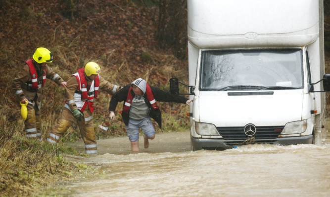 A man is helped out of his van after the River Teviot in Hawick broke its banks. The Borders and northern England were worst hit on Saturday.