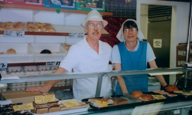 The McEwens behind the counter of their shop.