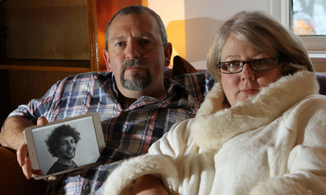 Gregs parents, Peter and Tina Boswell, with a picture of their son.