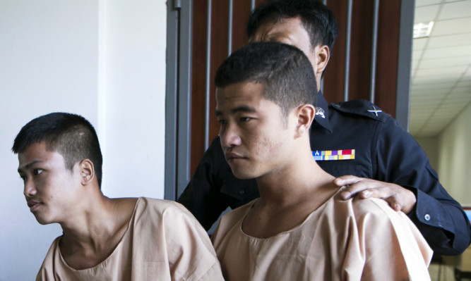 Myanmar migrants Win Zaw Htun (right) and Zaw Lin are escorted by officials after their guilty verdict at court in Koh Samui.