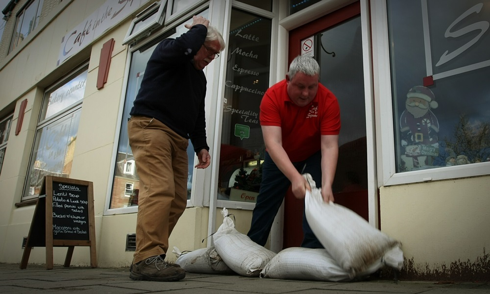 COURIER, DOUGIE NICOLSON, 29/12/15, NEWS. Cllr Dennis Melloy helps Steven Boath, owner of the Cafe In The Square in Alyth, put some sandbags in the doorway of the cafe today, Tuesday 29th December 2015, as the town braces itself ahead of Storm Frank. Story by Perth office.