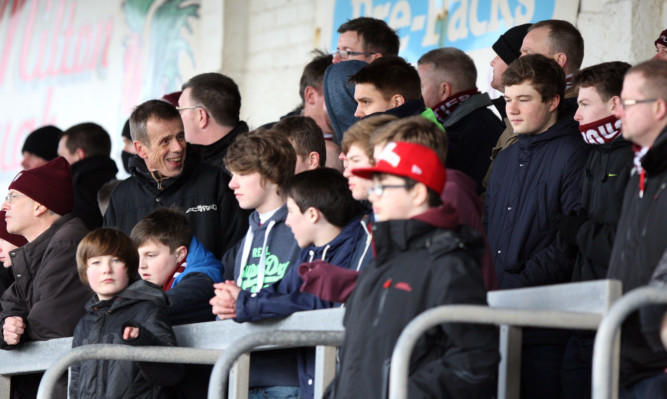 Kris Miller, Courier, 22/02/14. Picture today at Gayfield, Arbroath where filming was taking place for a series on footballs foreign outposts. Pic shows Tom Watts (former Eastenders actor) in the stands with fans at Arbroath Football Club.