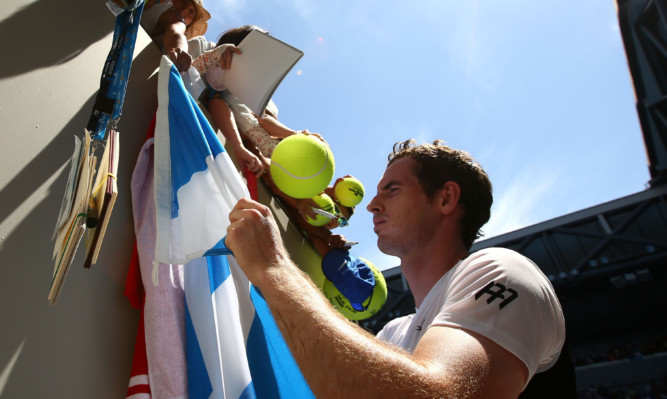 Andy Murray signs autographs after winning his first round match against Alexander Zverev.