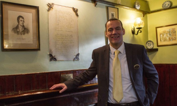 Kenmore Hotel manager Ross McEwan with the framed  Burns poem on the chimney breast.