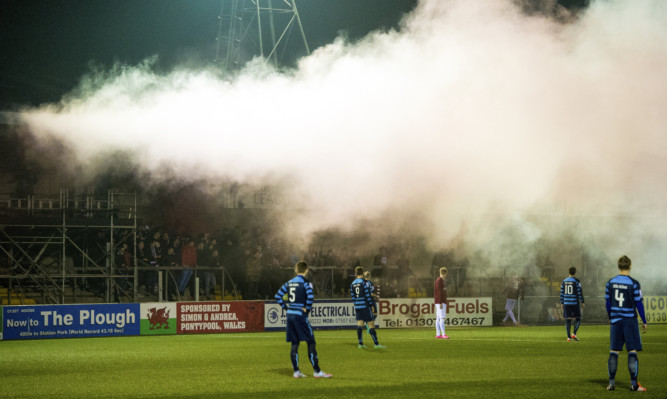 The match was called off after visiting fans set off flares and smoke bombs at Station Park.