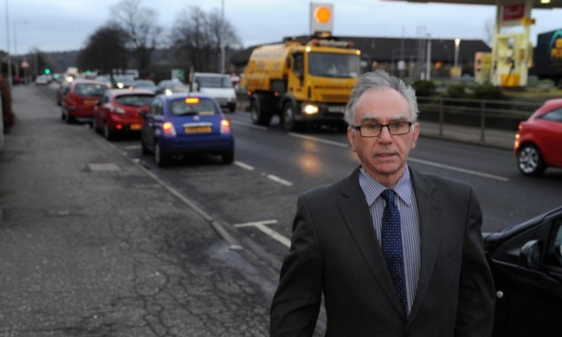 Cllr Mike Shirkie next to the traffic at Admiralty Road,.