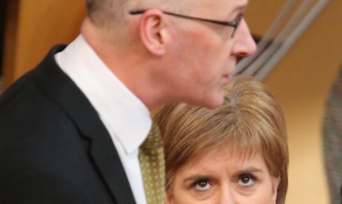 Nicola Sturgeon watches John Swinney in action at the Scottish Parliament.