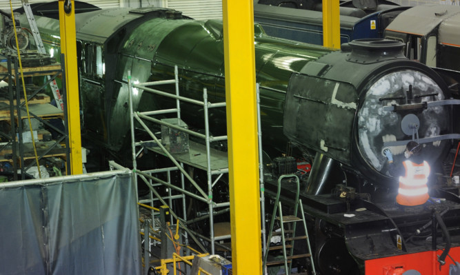 Alterations are made to the Flying Scotsman, freshly painted in green livery ahead of its official return to steam next week, in a workshop at the National Railway Museum in York.