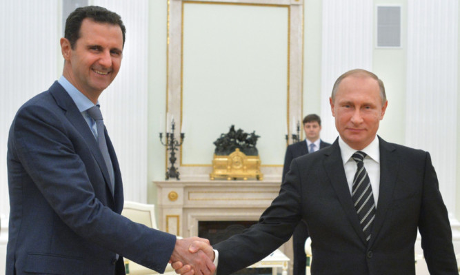 Presidents Assad and Putin shake hands  but just what are Putins intentions?