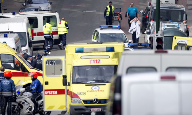 Emergency services evacuate a victim wrapped in a blanket after a explosion in a main metro station in Brussels.