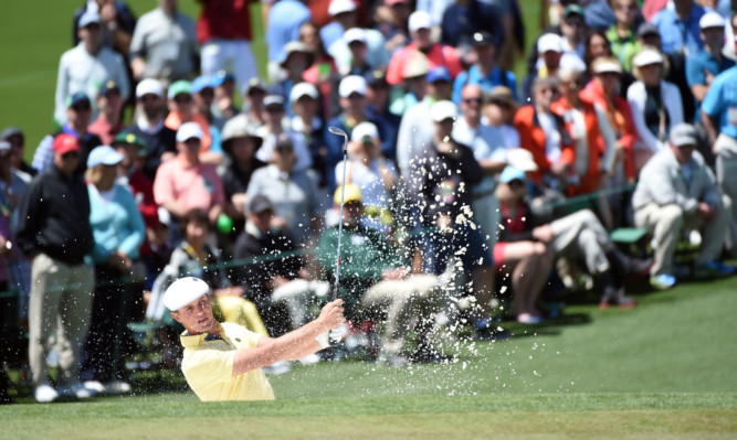 Amateur Bryson DeChambeau of the United States escapes from a bunker on the second hole.
