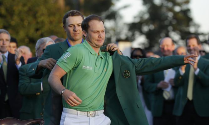 Jordan Spieth helps Danny Willett put on his green jacket.