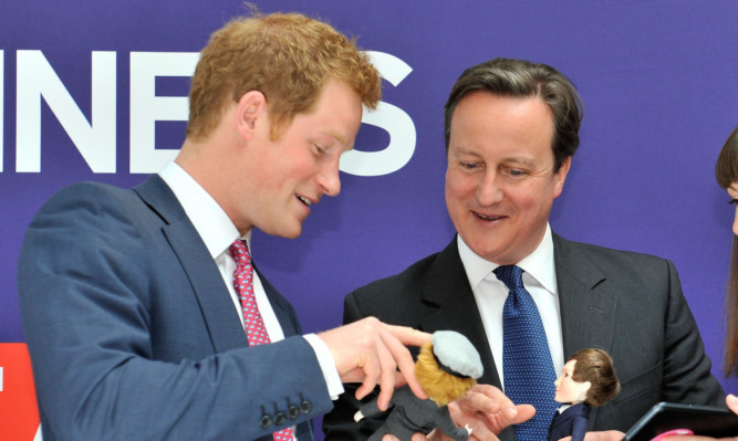Prince Harry and David Cameron are presented with dolls of themselves created by UK firm Makies.
