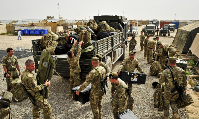 Troops from 1 Scots load gear onto a truck ready to depart camp Toombstone, Afghanistan, where they are leaving theatre after their tour of duty in the Brigade Advisory Group to fly back to the UK. PRESS ASSOCIATION Photo. Picture date: Sunday April, 7, 2013. See PA story DEFENCE Afghanistan Scots. Photo credit should read: Ben Birchall/PA Wire