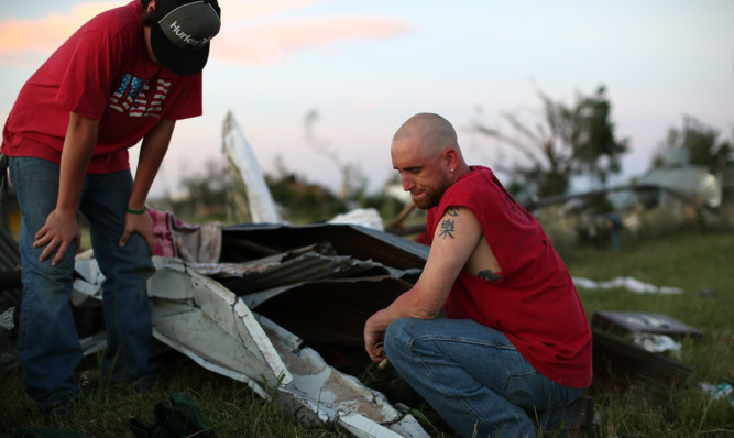 Locals pause while looking through debris after a series of tornadoes ripped through El Reno, Oklahoma.