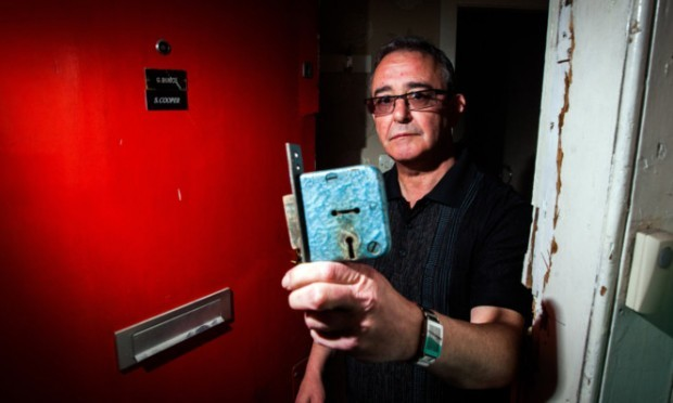 Gordon Bunce standing at his door in Garland Place, which has been smashed in, without repair, for more than two weeks.