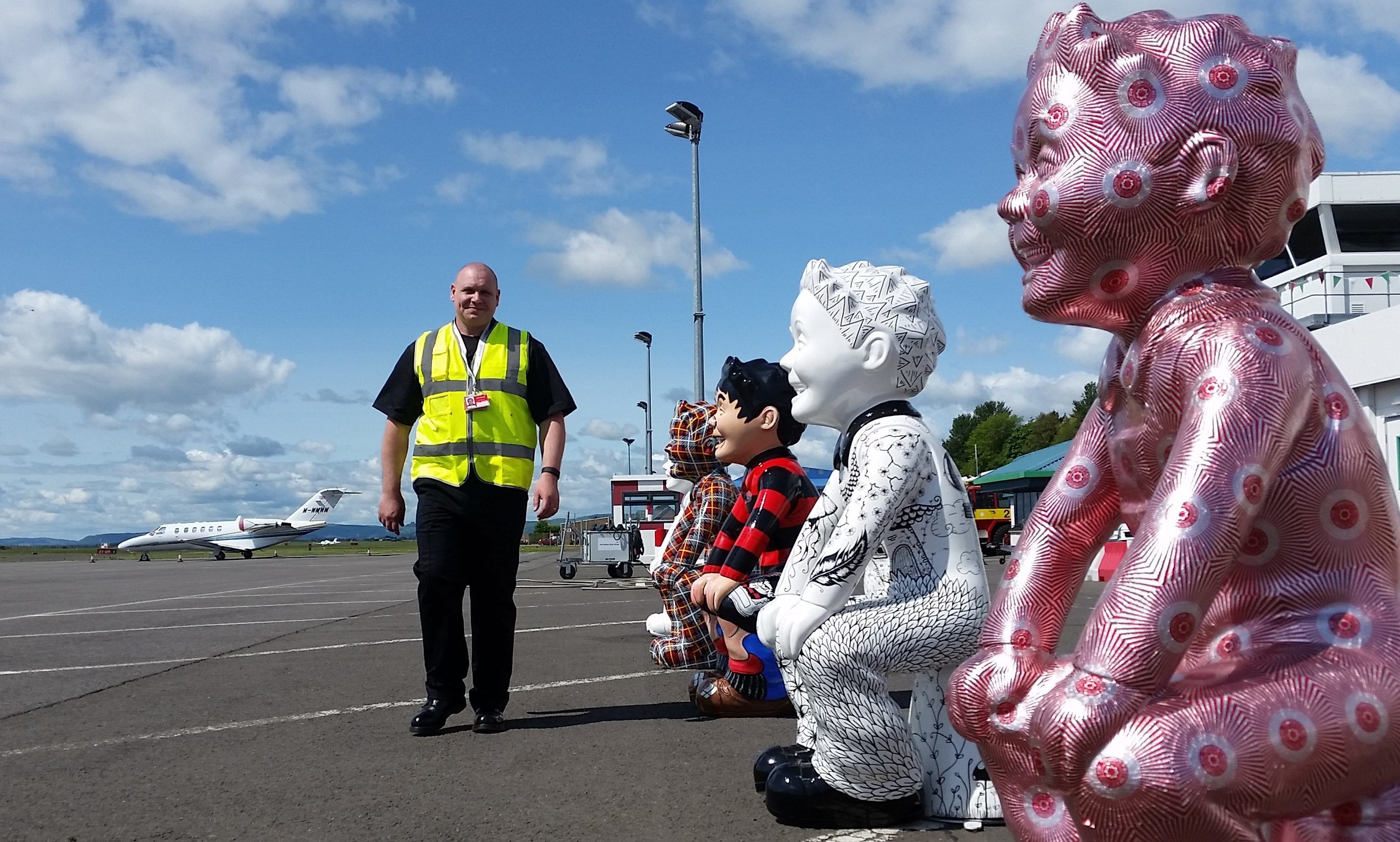 Crew manager Scott Raynor walks past an Oor Wullie guard of honour awaiting the first flight from Amsterdam.
