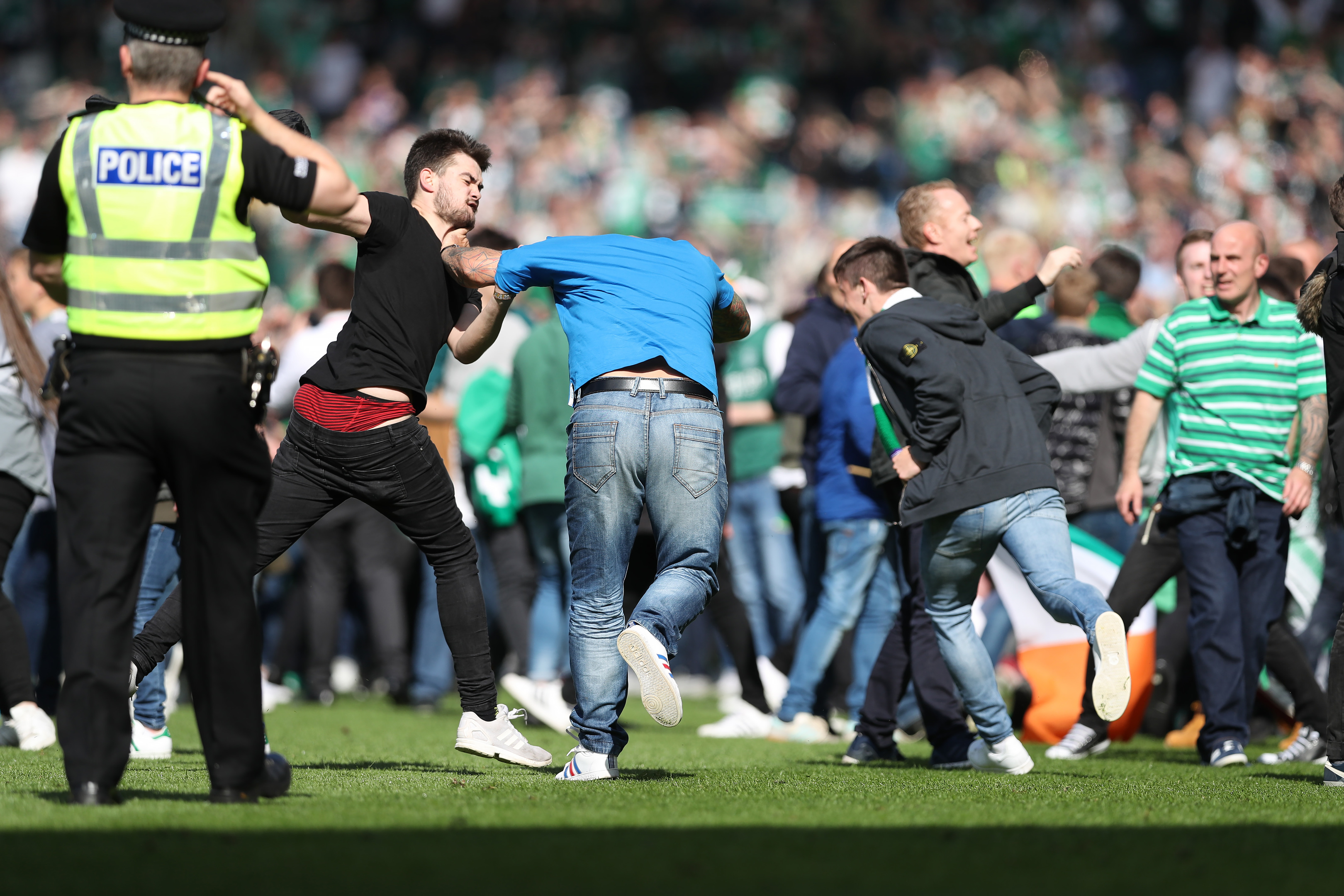 Hibs fans invade the pitch after the final whistle.
