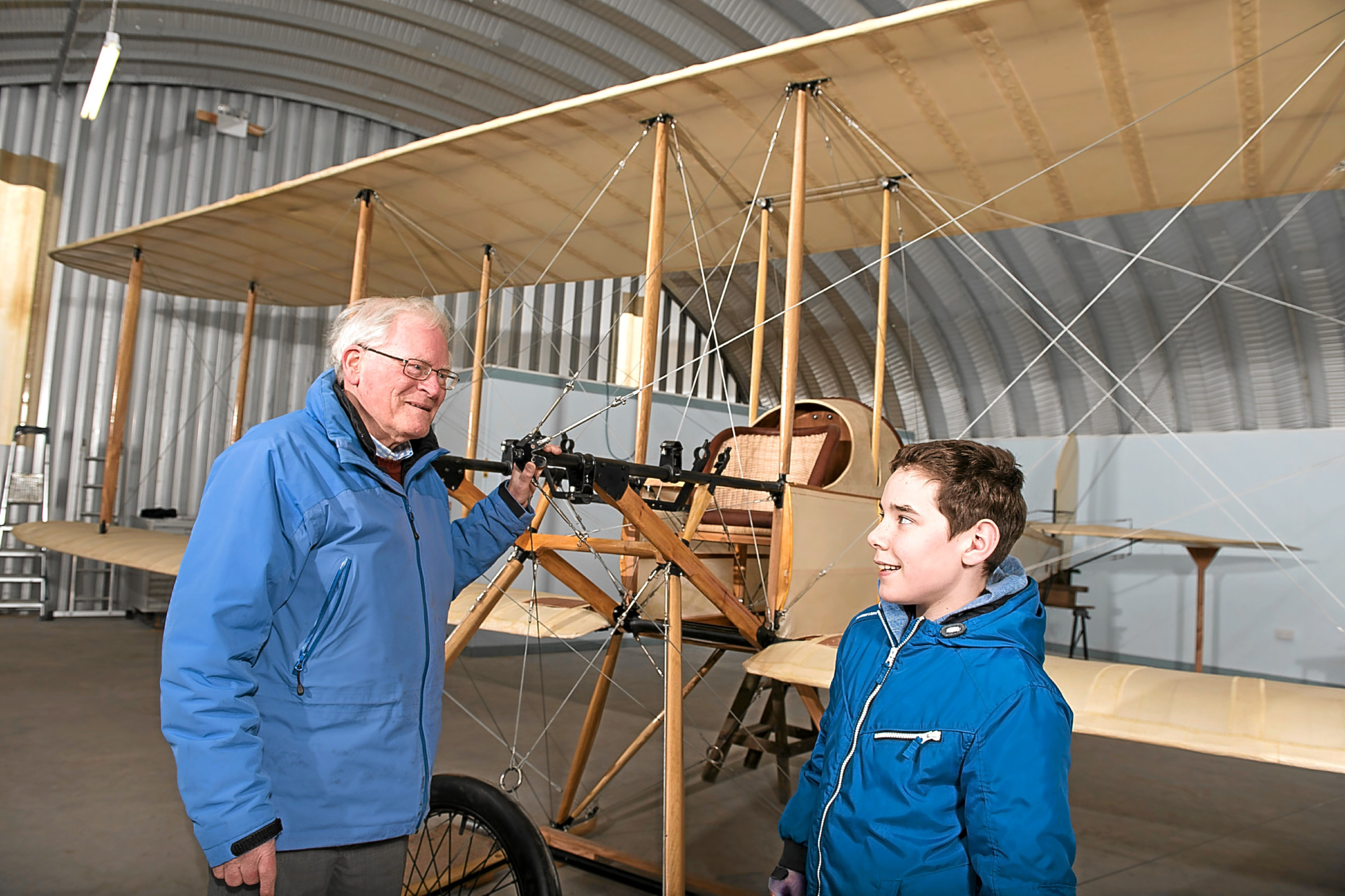 Alan Doe, chairman of the Montrose Air Station Heritage Centre, speaks to youngster Justine Paton beisde the replica BE2 plane.