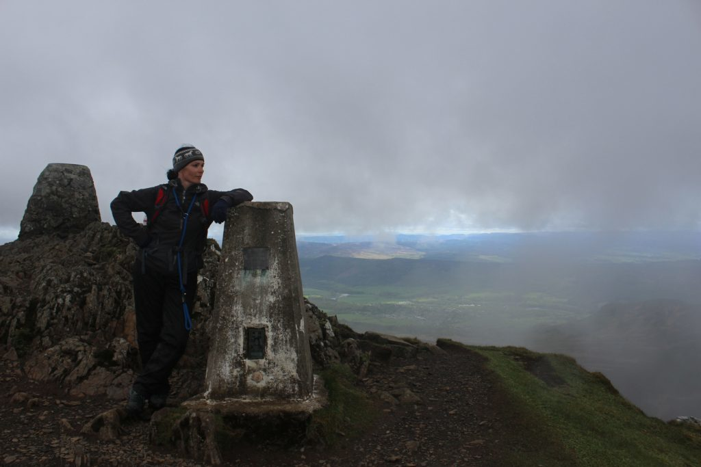 Gayle enjoys the misty view from the trig pillar on Ben Vrackie.