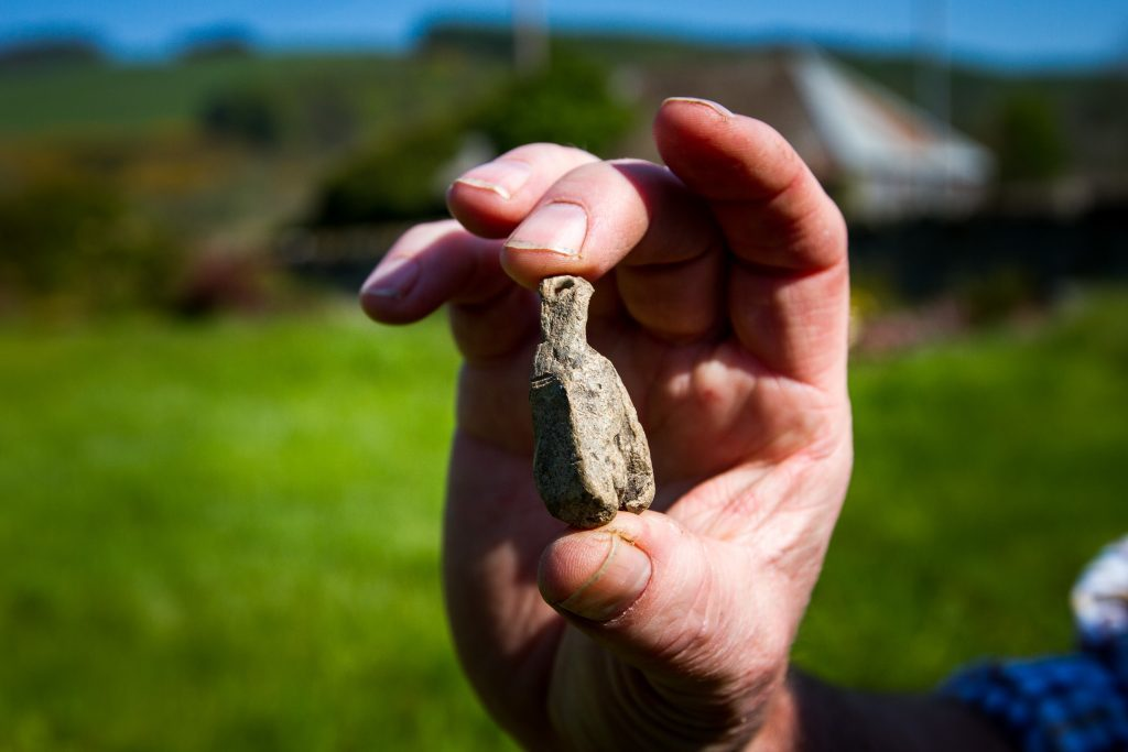 Drew McKenzie Smith holds a medieval 'plumb-line' found at the site.