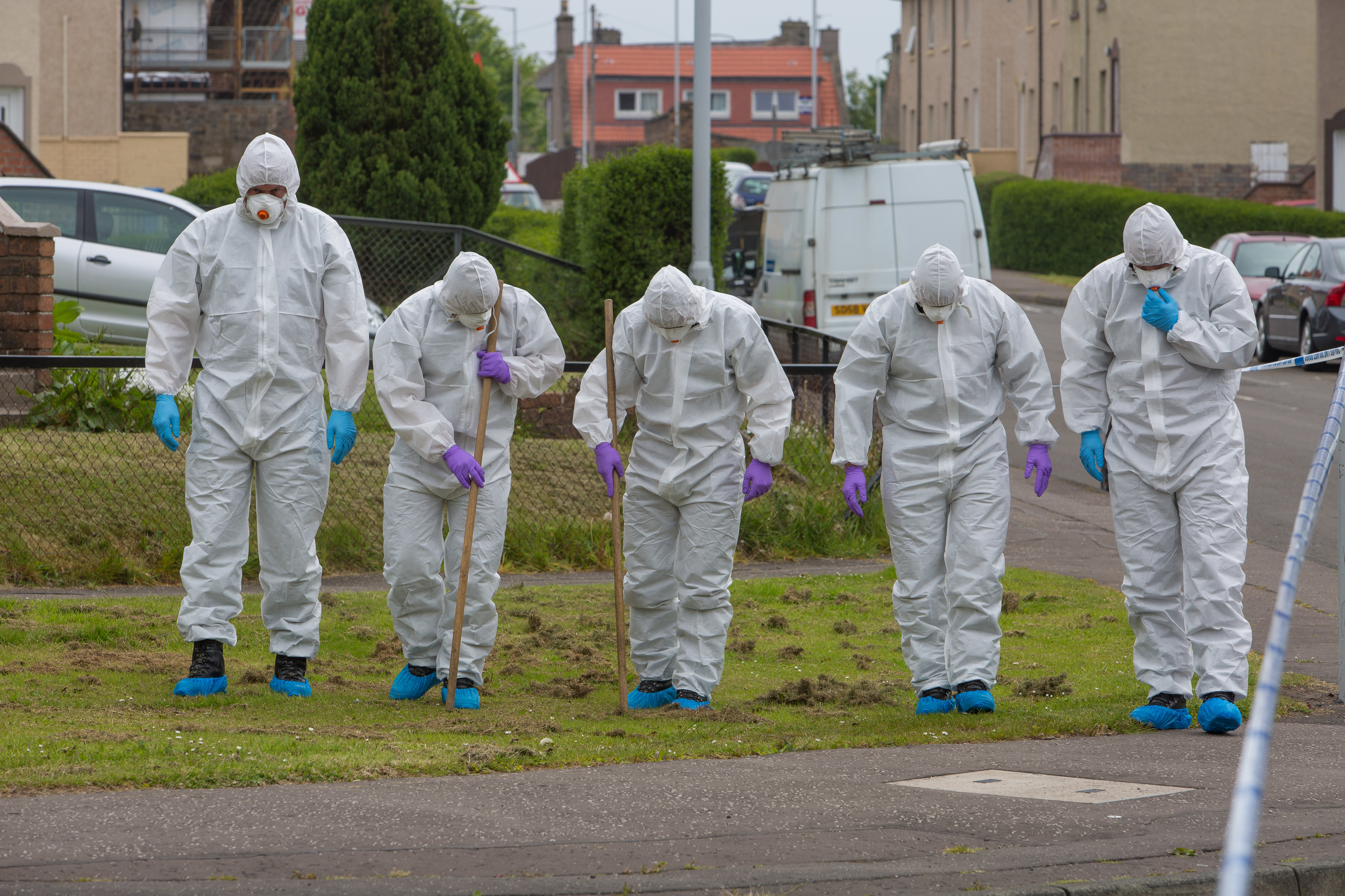 Officers conduct a forensic search of the scene.