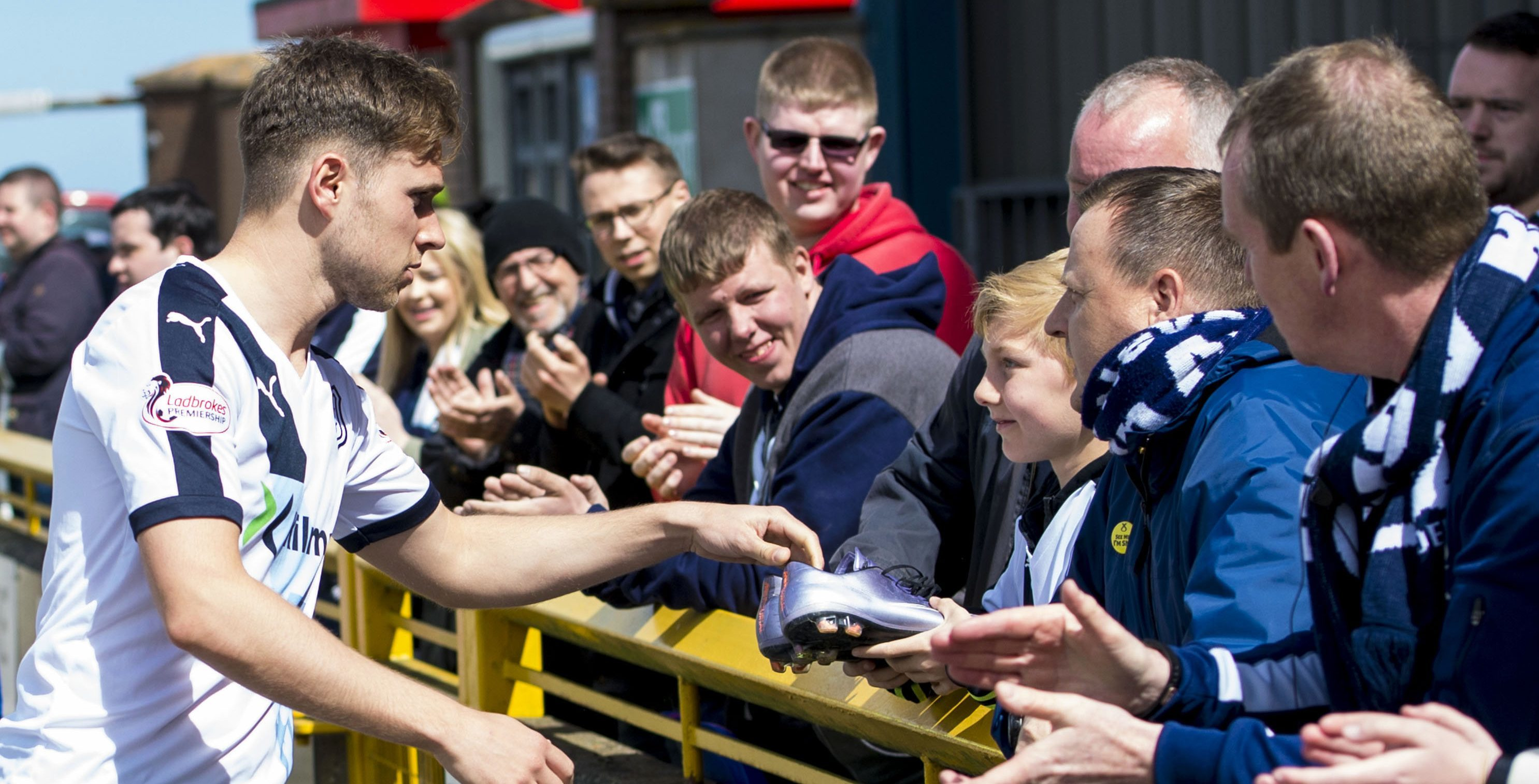 Greg Stewart giving his boots to a Dundee fan at the end of their last game of the season at Inverness on Saturday.