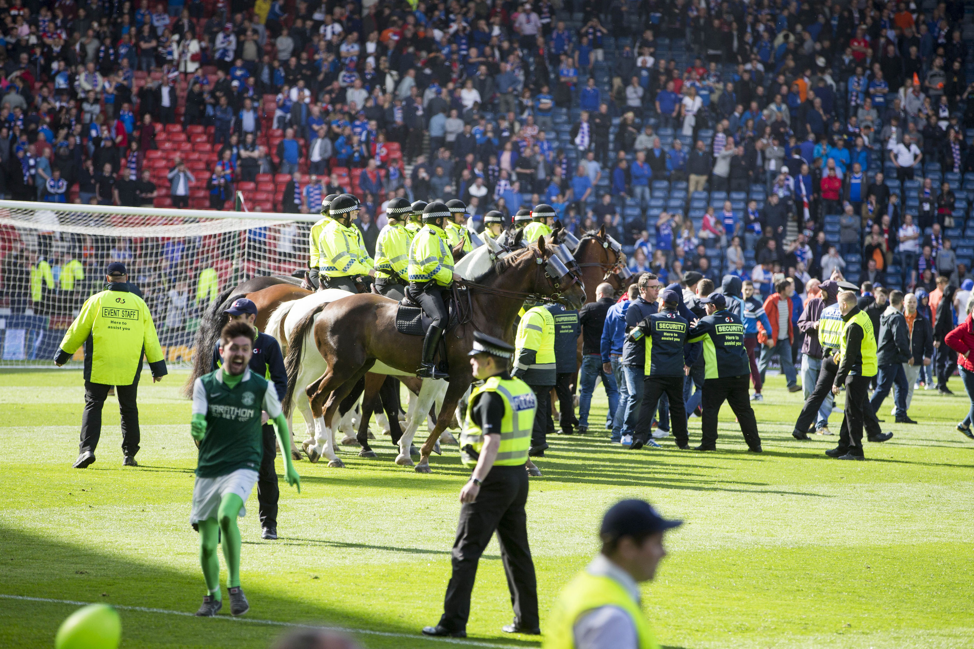 Police horses trying to guide fans off the pitch.